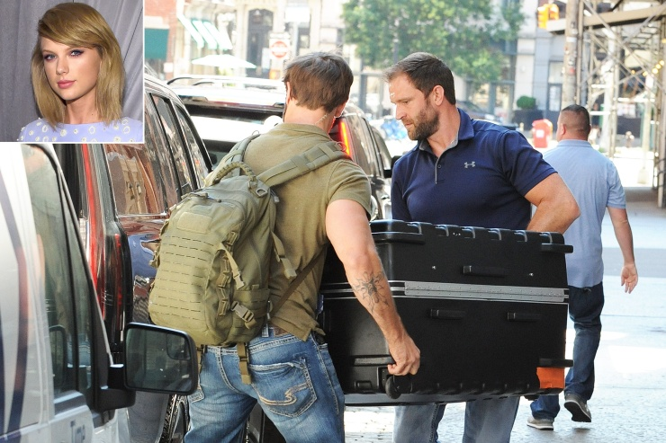 Taylor Swift's security guards are seen moving a huge case into the truck of an awaiting SUV.